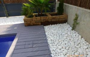 Jardín con tarima sintética, piedra decorativa y jardineras de tufo