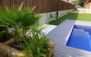 Jardín sostenible con tarima sintética, bolo decorativo y césped artificial